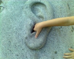 """Lend me your ear"" - Small hand in the ear of the sculpture titled ""Listening Stone"" by Joseph Wheelwright"