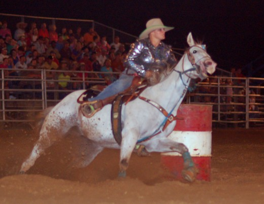One of the cowgirls making the turn around the last barrel.