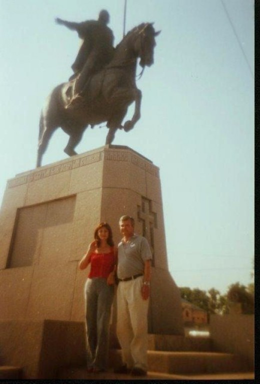 My wife and I posing beneath the Statute of Alexander Nevsky a thirteenth century Russian military hero and Prince of nearby Novogorod
