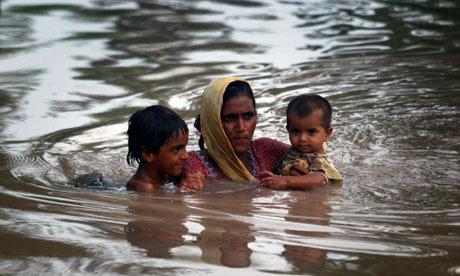 Woman saving her children from flood water in Shikarpur Talka