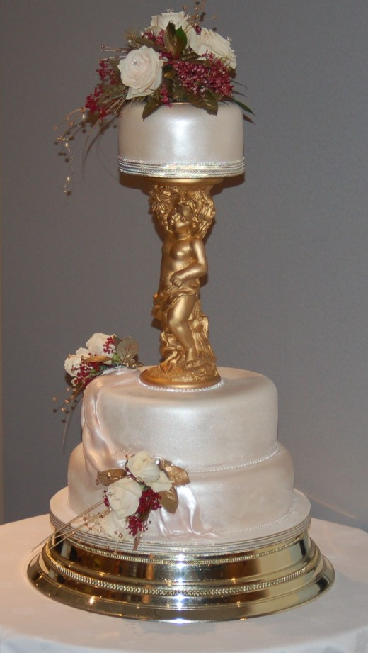 A 3 Tiered Wedding Cake airbrushed with a satin finish , cream roses with burgundy gyp and gold leaves