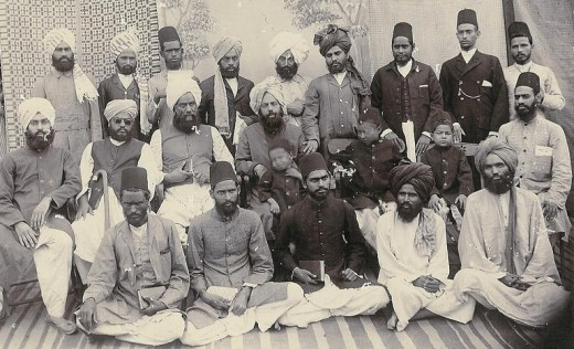 Mizra Ghulam Ahmad is in the center with a child on his lap.
