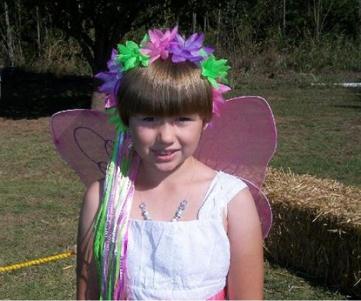 This cute butterfly costumed child was given a special colorful headdress by a relative.  She was quiet, sweet, and enjoying the festivities.