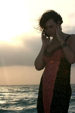 A young woman making a cellphone call from the beach. More than any cellphone call, prayers are never unanswered.