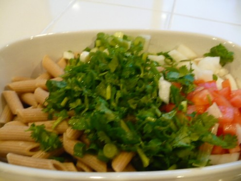 Put penne pasta, green onion, cilantro, chopped tomatoes in--ready to toss.