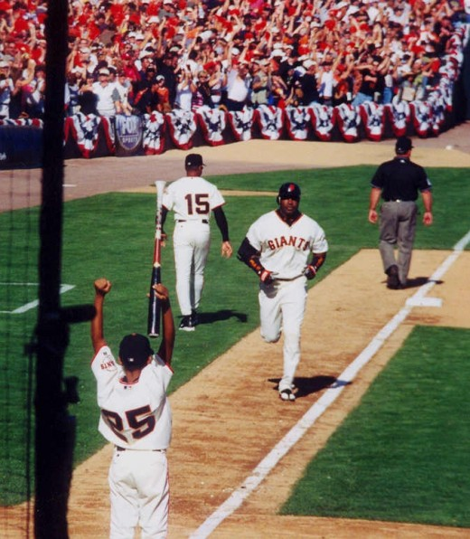 Barry bonds coming home after a hugh Homerun...DURING THE POSTSEASON  (see bunting behind him) his son awaits him at home plate.