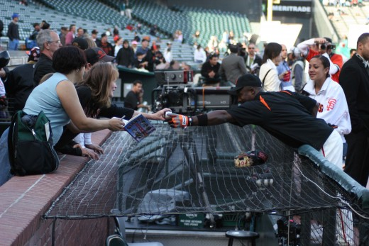 Fans getting autographers from players at the Giants' dugout.