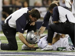Dallas Cowboys quarterback Tony Romo is tended to during the first half of against the New York Giants in an NFL football game Monday, Oct. 25, 2010, in Arlington, Texas. Romo was drilled into the turf on his left shoulder, forcing him to the locker