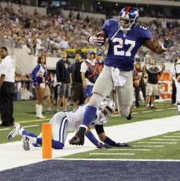 New York Giants running back Brandon Jacobs scores a touchdown as Dallas Cowboys safety Gerald Sensabaugh defends during the second half an NFL football game Monday, Oct. 25, 2010, in Arlington, Texas. New York won 41-35. (AP Photo/LM Otero)