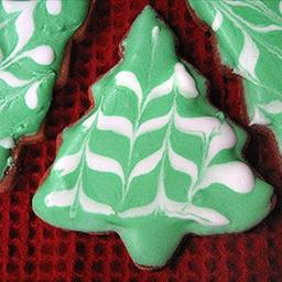 Chrismas tree cutout painted with Royal icing. Paint entire cookie with green (pour on or use soft pastry brush). Make decorative stripes with white while green is still wet.