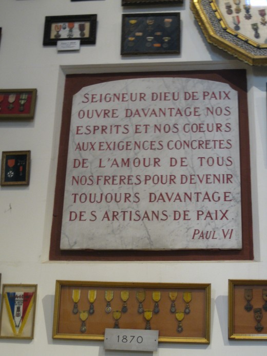 A quotation from Pope Paul VI and military medals from the Franco-Prussian War in 1870