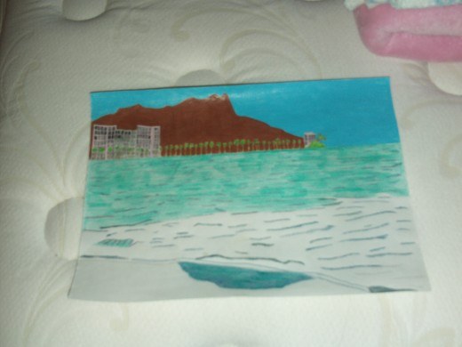 A darker blue colored pencils was used to go over the ripples of the wave, and an aqua colored pencil was used to fill in the rest of the ocean.  I used a black colored pencil to fill in the windows on the high rise hotels in the sketch.