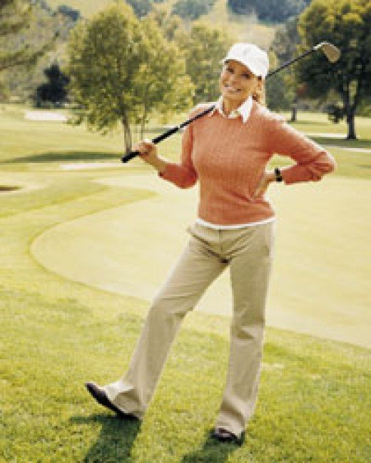 Cheryl Ladd in golfng attire and holding a golf club