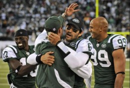 New York Jets quarterback Mark Sanchez (6) hugs offensive coordinator Brian Schottenheimer after throwing a touchdown-pass as teammates Santonio Holmes (10) and Jason Taylor (99) look on during the fourth quarter of an NFL football game against the H