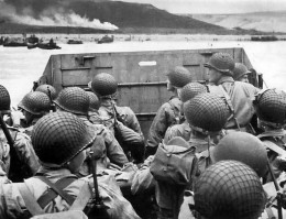 "Troops in an LCVP landing craft approaching ""Omaha"" Beach on ""D-Day"", 6 June 1944. Note helmet netting; faint ""No Smoking"" sign on the LCVP's ramp; and M1903 rifles and M1 carbines carried by some of these men."