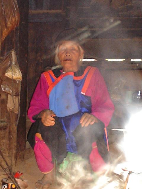 Beautiful Lisu Elder woman sitting beside the fire inside her home.