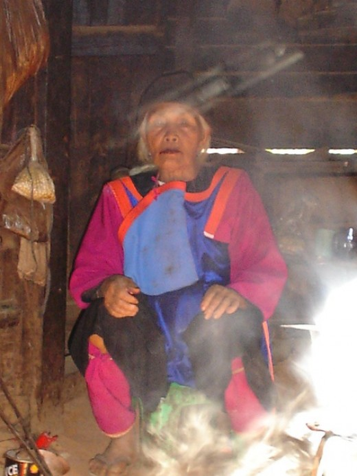 Beautiful Lisu Elder woman sitting beside the fire inside her home.