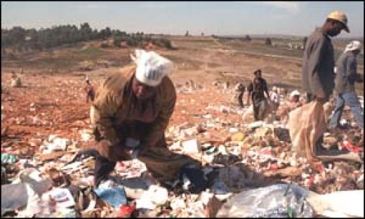 Woman searching for food on a landfill site