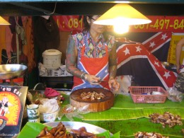 A beautiful tattooed lady butchering stewed pork - I wonder if she's single.