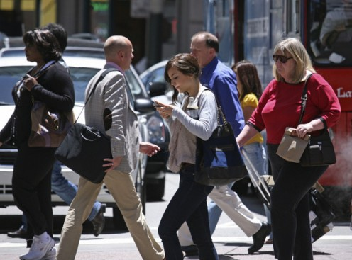 A woman text messages while walking across the street in San Francisco.  by Associated Press