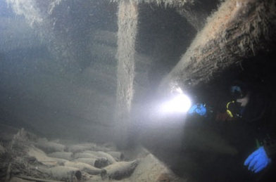 The bottles of the unique 200-year-old Veuve-Clicquot champagne lie neatly stacked inside the hull of the shipwreck at the bottom of the Baltic Sea near land, Finland.