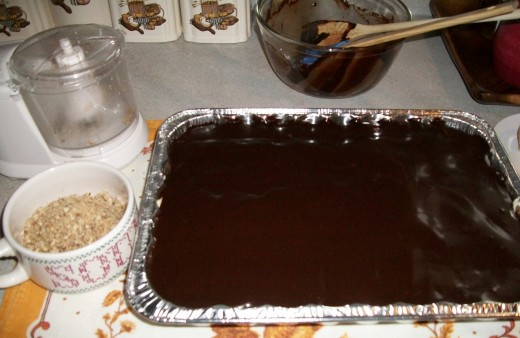 While the frosting is warm, spread it over the upper layer of the cake.