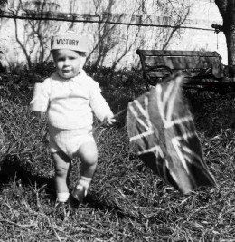 Me, evidently on VE Day, 1945 at the back of Queenie's house