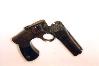 Revolving hammer pistol showing the hammer (left, inside) and the nipples for the percussion caps (right, inside).