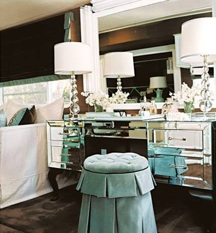 Mirrored furniture, crystal lamps, silk slipper stool all add up to comfortable glamor.