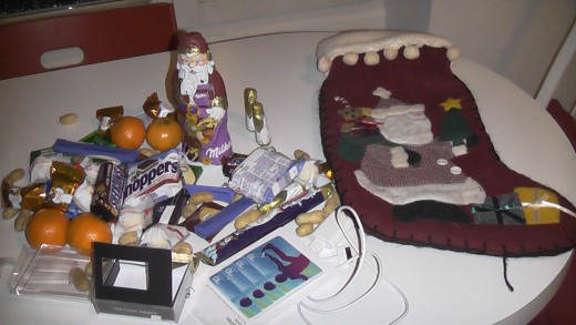 The contents of my son's stocking: candy, gift cards from iTunes, an adaptor for his iPad and fruit.