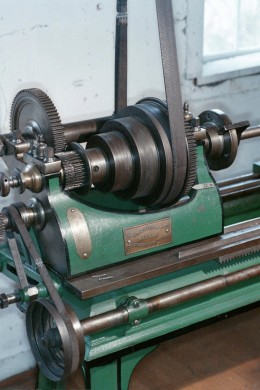 Drive belt and gearing on a barrel profiler.  Belt driven machines remained standard until the 20th century, although the motive source evolved from water, to steam, to electricity, and even internal combustion engines.