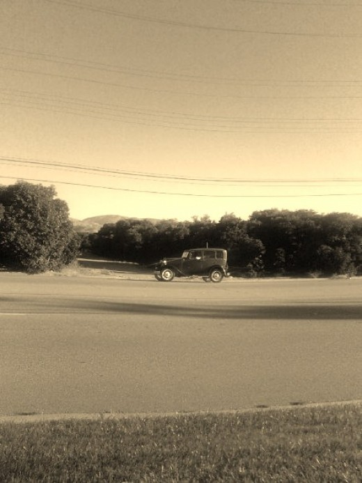 Car driving down a road near an orange field. This old fashion car and sepia imagery makes the picture look like it was taken before World War II, but it was really taken in July of 2009.