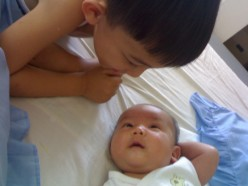 An older brother is talking to his baby brother, while the latter listens intently.