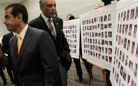 Los Angeles Mayor  Villaragoisa and Former LAPD Chief and now Los Angeles Council Member Parks look at the Grim Sleeper Photographs.