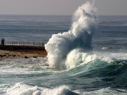 Waves crashing on rocks in La Jolla, while people are walking along a pier.  An amazing capture, in the public domain.
