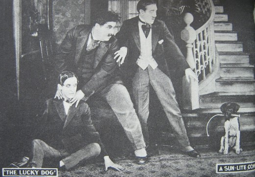 Lobby Card c. 1921 featuring the first appearance on film by Laurel and Hardy, in Lucky Dog produced in 1919 and released in 1921. Stan Laurel is seated with a mustachioed Oliver Hardy's hands around his neck.