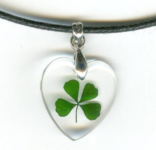 This beautiful Celtic necklace contains a genuine four leaf clover frozen in clear acrylic polyresin suspended on a black cord necklace. Pendant is about the size of a dime.
