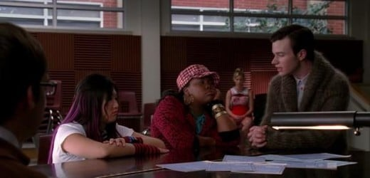 Kurt devising a plan to get him, Tina, Mercedes and Artie on the Glist with Brittany in the background