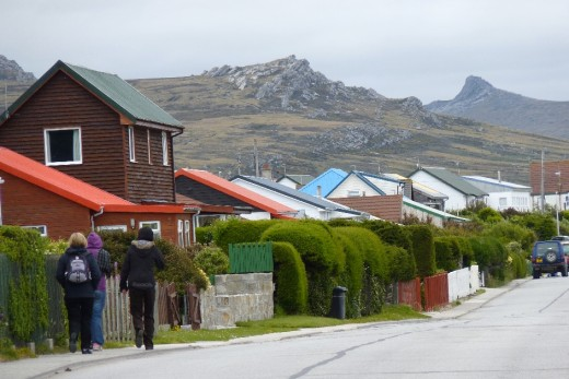 A typical scene in Stanley with colourful houses and the barren landscape beyond.