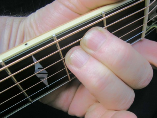 Em chord being fingered on the guitar
