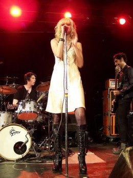 Taylor Momsen in black and white with boots, performing on stage with The Pretty Reckless