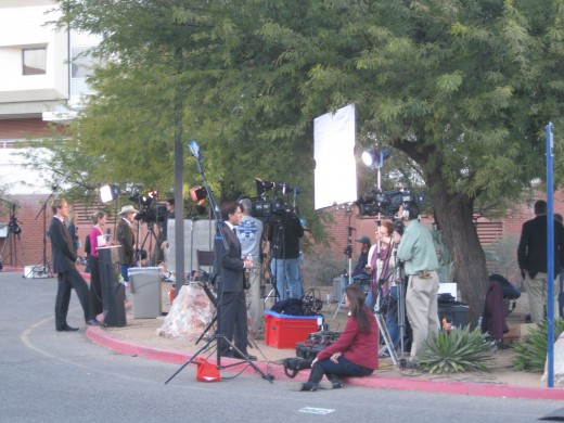 Reporters giving live reports from the press area in front of University Medical Center in Tucson, AZ