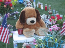 A teddy bear continues to sit silently as dusk begins to fall.