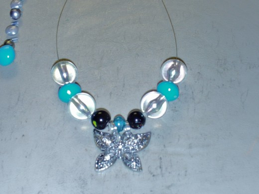 Continuing the pattern by adding another clear large acrylic bead to each side of the necklace.