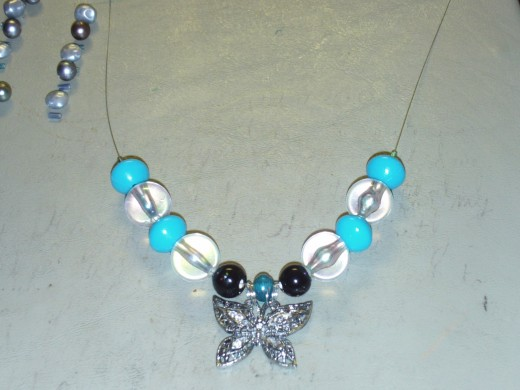 Here I am adding one large aqua vintage bead to each side of the necklace.