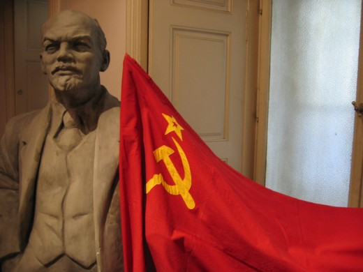 Statue of Vladamir Ilyich Lenin beside Soviet flag.  He was a marxist revolutionary and leader of the Bolshevik Revolution of 1917.  He was the first leader of Communist Russia (USSR).  It is estimated 1.5-6 million died violently during his rule.