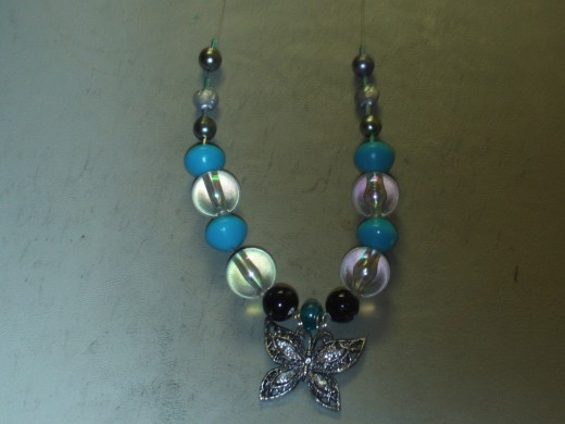 Here I add another small glass cylinder bead to each side of the necklace.