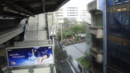 View of cafe from Skytrain exit.  The coffee shop is in the tree area in front of the tall buildings in the picture.