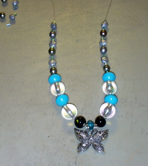 Here I added another glass cylinder bead to each side of the necklace.