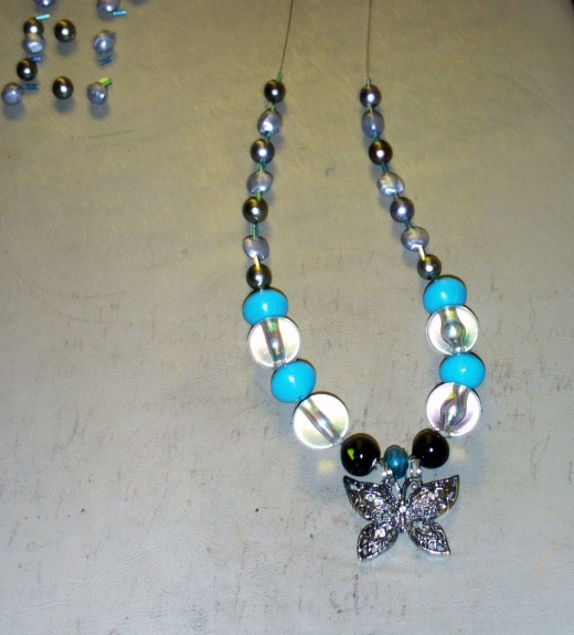 Here I added one glass cylinder bead to each side of the necklace.